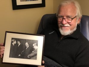 Lars Sandven '69 holds photo of himself standing with King Olav V of Norway who visited Augsburg in 1968.