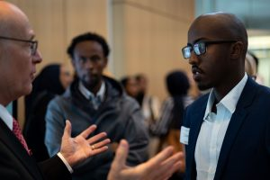 Two students talk with Fuad after his presentation