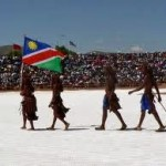 four people walk with Namibian flag
