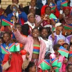 Crowd cheers and waves Namibian flags
