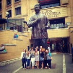 Group poses in front of Nelson Mandela statue