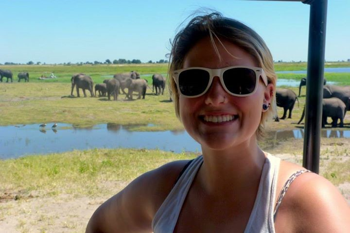 Student poses with elephants in background