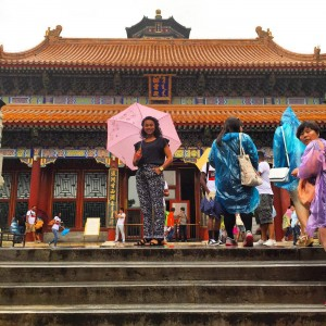 woman stands holding an umbrella in front of chinese temple
