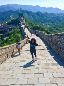 woman stands with arms outstretched on great wall of chine