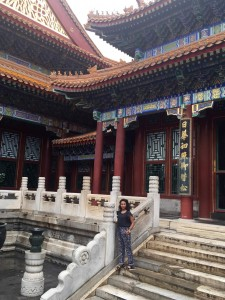 woman stands in front of traditional chinese temple