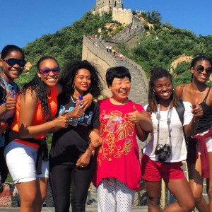 group of young people stand in front of great wall of china