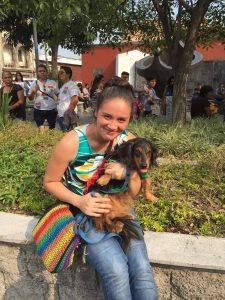 young woman holds dog while wearing rainbow gear