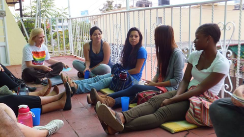Students sitting outside along balcony