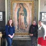 Students stand in front of a painting of the Virgin Mary
