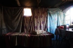 a small room with floral sheets draped over the walls