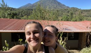 Two young women smile for a selfie in front of a mountainous background