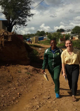 two smiling young woman walk side by side on a winding dirt road