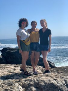three women stand on a large rock with the blue ocean behind them