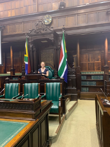 A woman sits in a large chambers seat with the flag of South Africa on either side of her