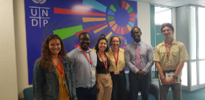 six people wearing lanyards stand in front of a UNDP mural
