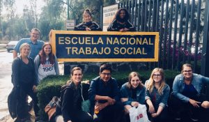 students pose by a sign that reads escuela nacional trabajo social