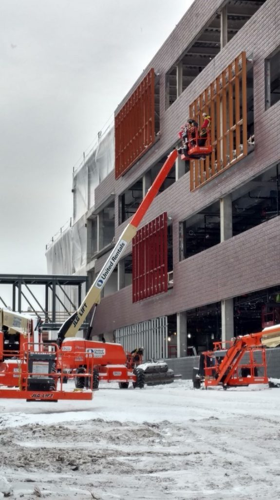 Construction crews install the accent-colored window frames on the Hagfors Center.