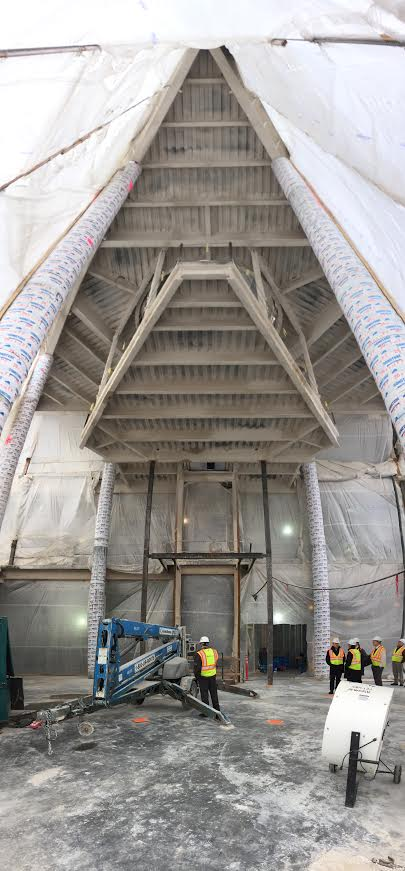 This image, inside the lobby area of the Hagfors Center, shows the floor of the suspended chapel and the ceiling above it after fireproofing has been completed.