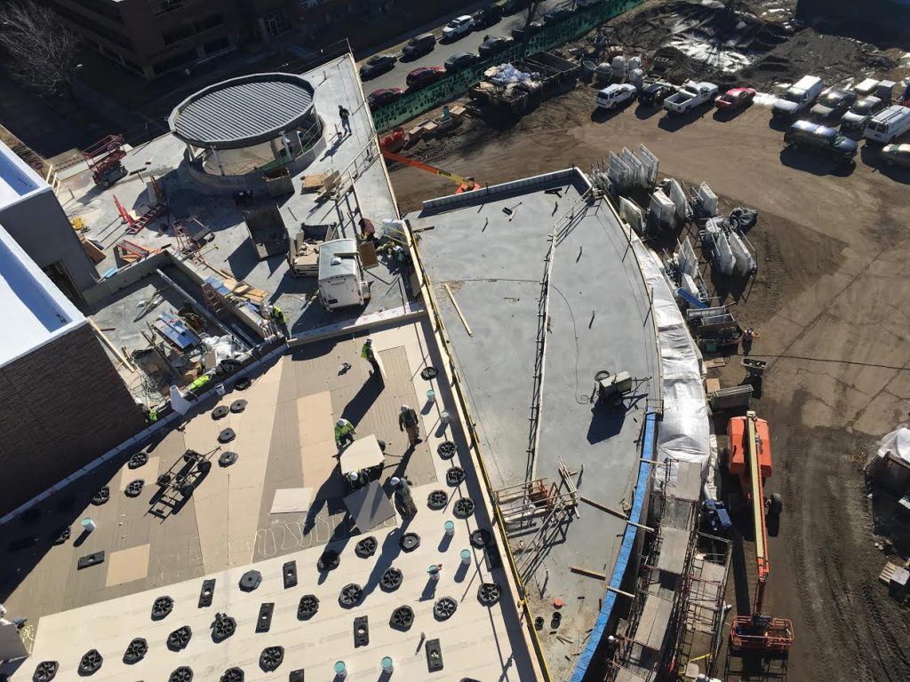 Crews install the final roofing layer on the west wing and around the suspended chapel.