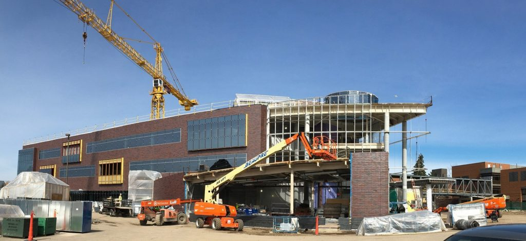 This view of the south side of the Hagfors Center shows the progress of the hand-laid brick on the flexible classroom and the structural framework for the lobby curtainwall.