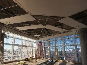 Ceiling grid and tile installation in progress in the lobby