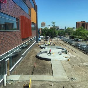 Concrete walkways are under construction to connect the outdoor seating area east of the building.