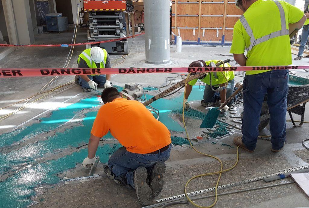 Crews pour the terrazzo lobby floor