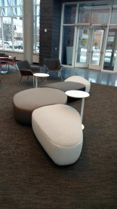 Upholstered seating with no backs and small round tables