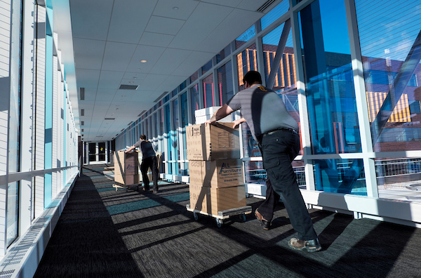Movers pushing boxes on dollies through the skyway