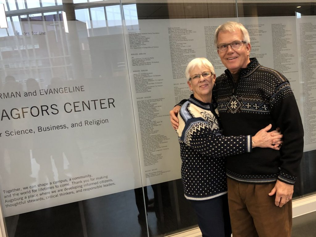 Man and woman wearing Norwegian sweaters in front of wall of donor names