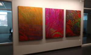 Three-piece art installation in oranges, pinks and reds, on a wall