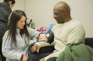 nurse performs blood pressure check