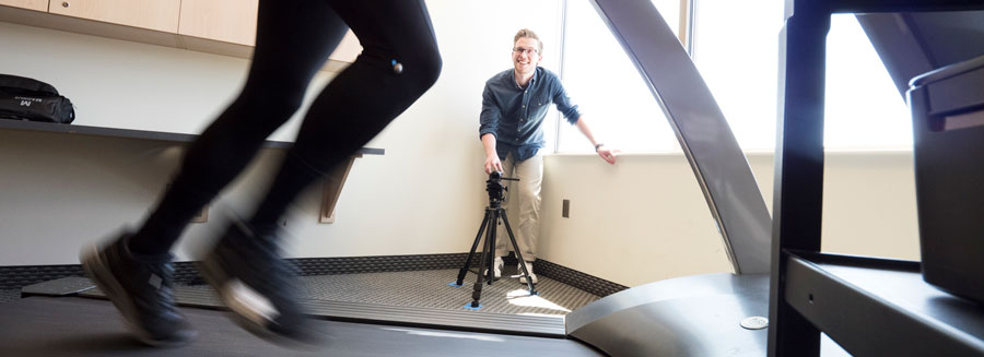 student filming someone running on a treadmill