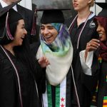 Three students exchange smiles in graduation gear.