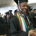 Student in graduation gown and graduation honors smiling before ceremony.