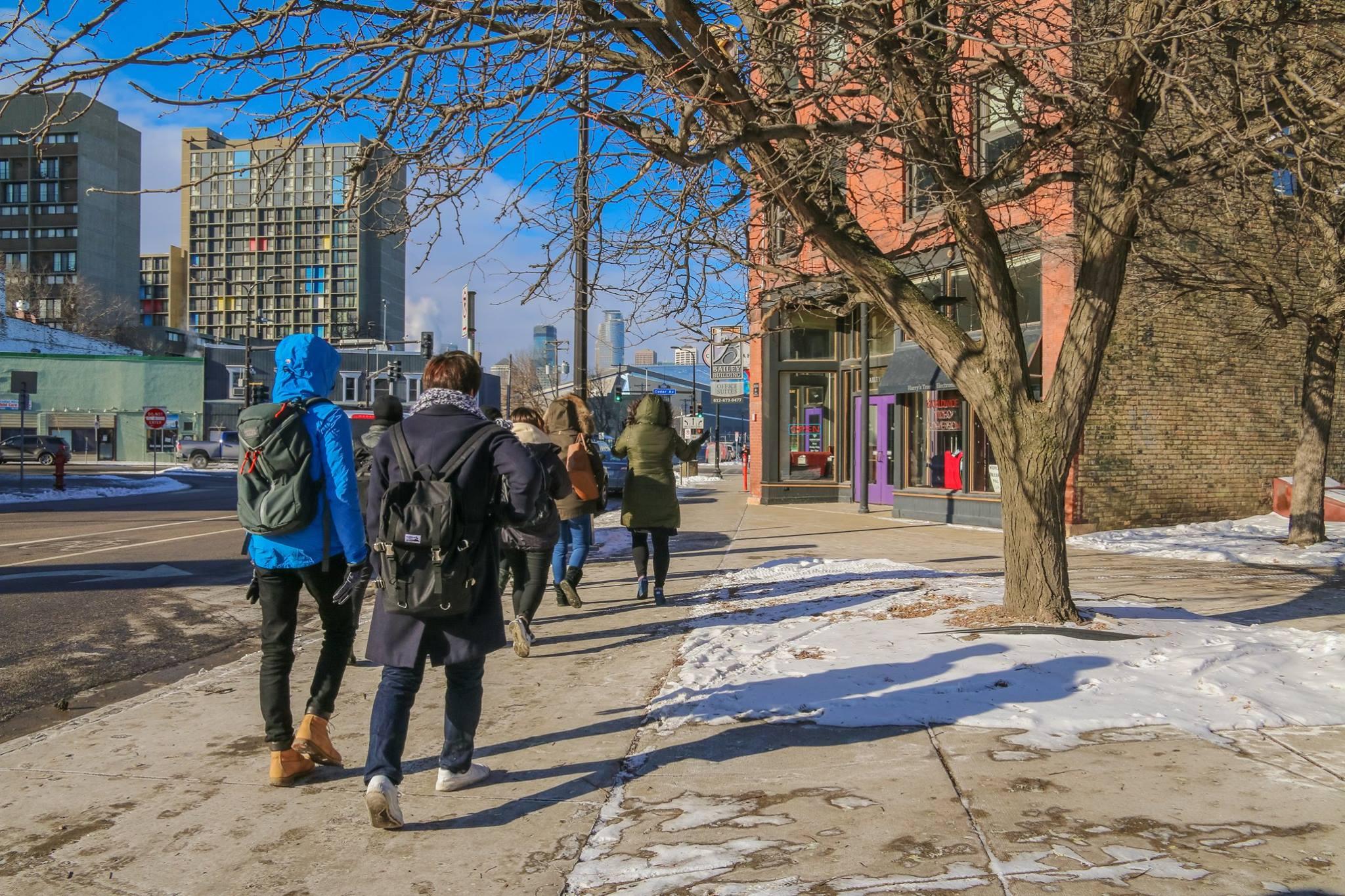 A group of new international students walk through Cedar Riverside.
