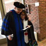 Student and professor embrace in graduation gowns.