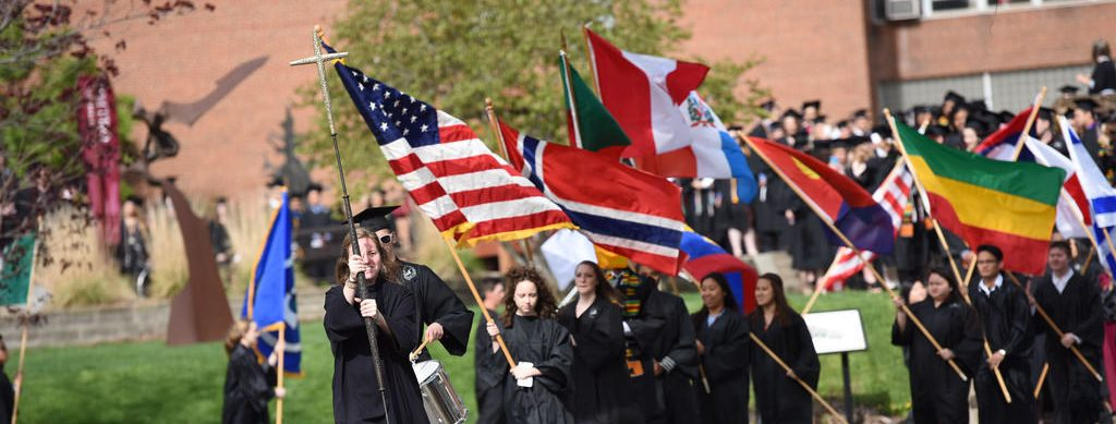 Students carry flags into graduation ceremony at Augsburg University.