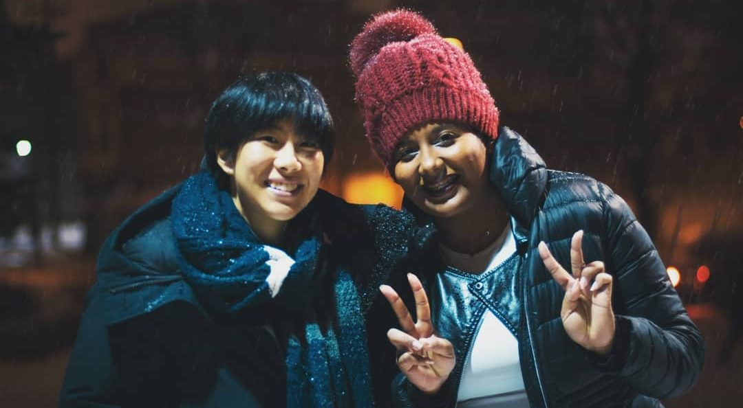 Two students pose in the snow at Augsburg University