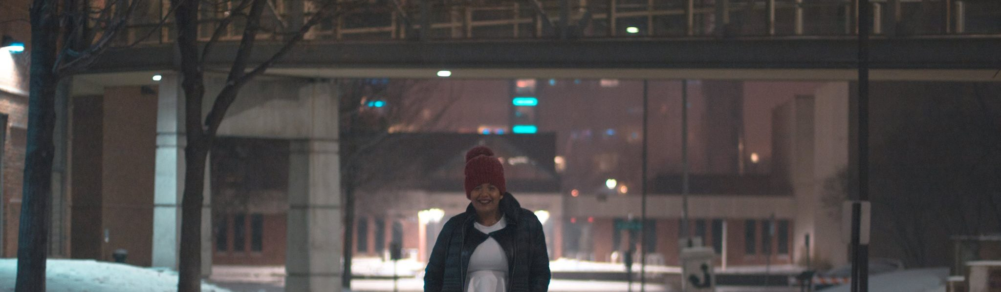 Exchange student poses under one of many skyways at Augsburg University in the snow.