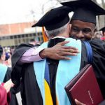 Student and professor embrace with graduation diploma.