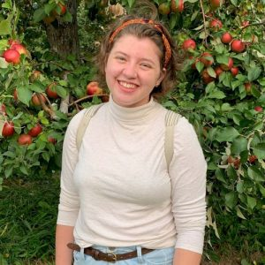 Woman in a white turtleneck in front of an apple tree
