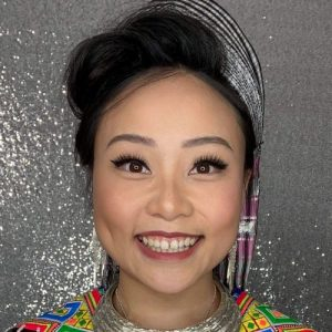 Woman in traditional Hmong dress in front of a silver backdrop