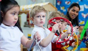 Nursery children playing with musical instruments in the classroom. One little boy is looking at the camera with a tambourine.