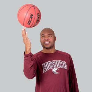 Devean George holding a basketball with the tip of his fingers in a grey background