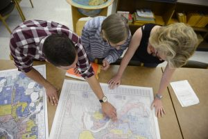 Three researchers looking at a paper map of Minneapolis