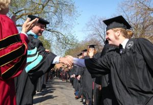 English major Connor Doebbert shaking hands with Prof. George Dierberger at Augsburg's 2017 spring commencement.