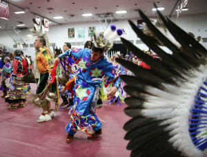 Native Americans dancing in traditional clothing in the Augsburg Gym