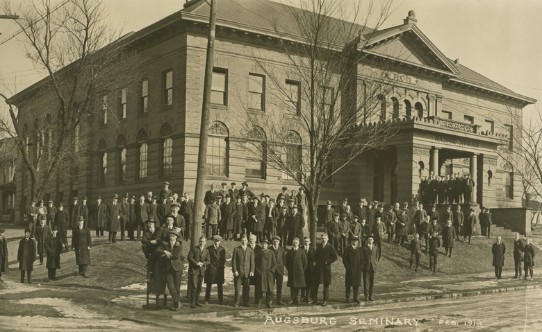The group photograph shows the Augsburg Seminary community in February 1918. At that time, Augsburg Seminary had three areas of focus—a theological school, a college, and a preparatory department.