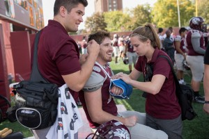 Student Sports Medicine Assistants Jack Duffy '16 (left) and Alison Ranum '17 (right) aid Auggie running back Michael Busch '16.